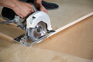 a man using a cutting tool to cut different sizes of plywood